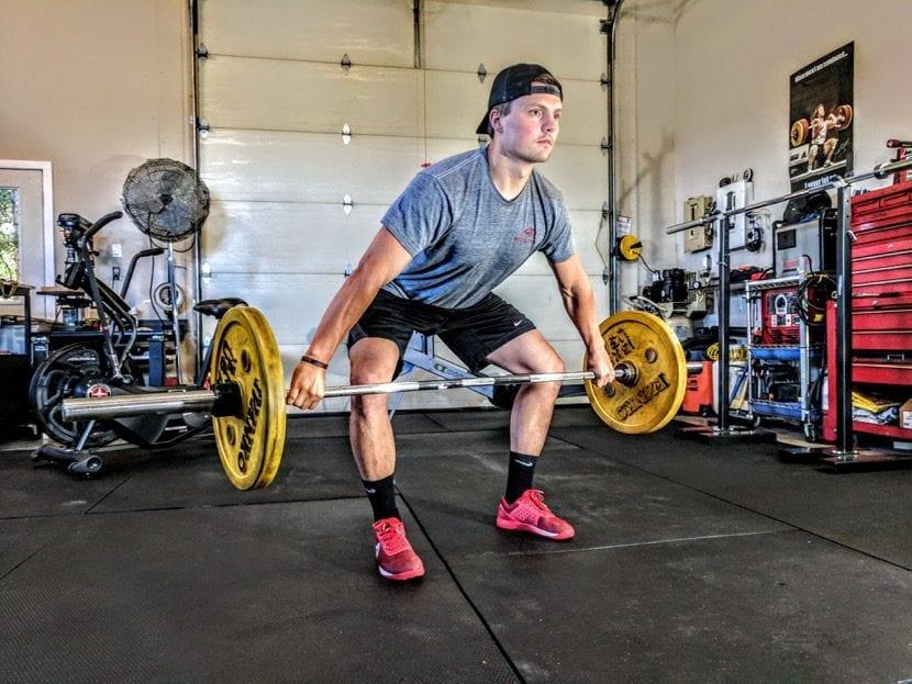 levantando pesas en el gimnasio de casa con suelo de goma